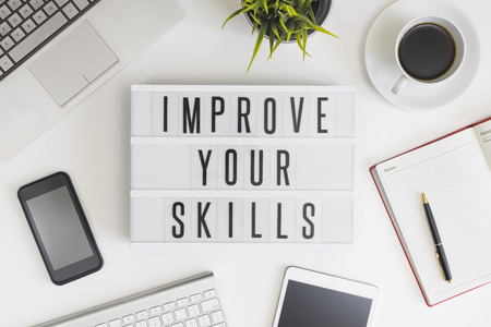 Improve your skills word on office table with computer, coffee, notepad, smartphone and digital tablet