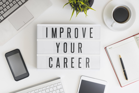 Improve your career word on office table with computer, coffee, notepad, smartphone and digital tablet