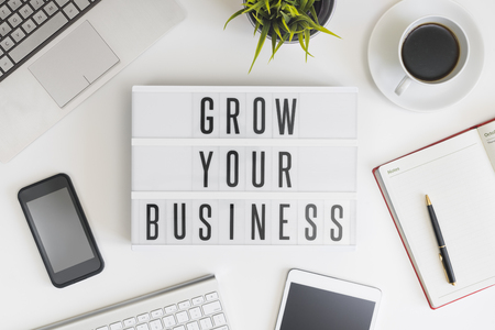 Erweitern Sie Ihr Geschäft Worten auf Bürotisch mit Computer, Kaffee, Notizblock, Smartphone und digitale Tablet