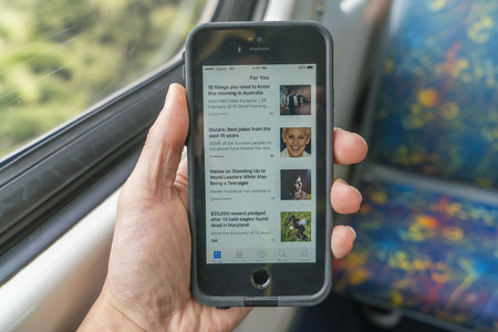 onboard: Melbourne, Australia - Feb 26, 2016: Using the News app on an iPhone onboard a train during commuting