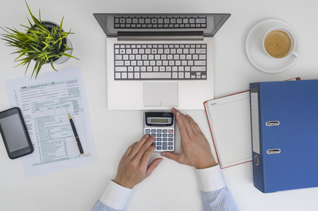top down: Businessman making calculation and filling tax form at office desk