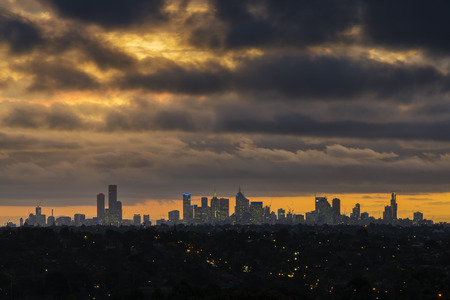 storm clouds: City skyline at sunset against storm clouds