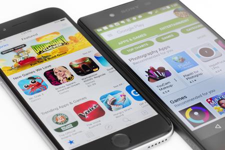play: Melbourne, Australia - 23 de mayo, 2016: Primer plano de Google Play Store en el teléfono inteligente Android y la tienda de aplicaciones de Apple en el iPhone. Ambas tiendas permiten a los usuarios descargar aplicaciones, música, películas y programas de televisión.
