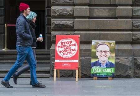 encuestando: Melbourne, Australia - 2 Jul, 2016: La gente que camina lugar de votación pase en Melbourne durante la elección federal de Australia 2016, con carteles de promoción de los candidatos de los partidos del Trabajo y verdes.