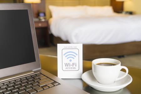 cama: habitación de hotel con el signo de acceso wifi, ordenador portátil y una taza de café