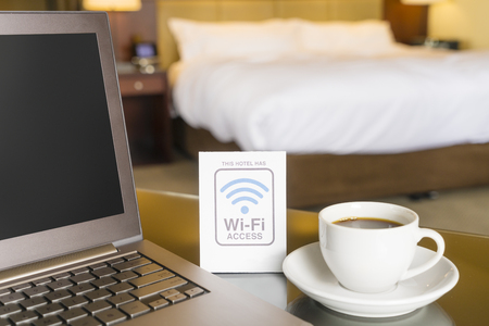 room access: Hotel room with wifi access sign, laptop and cup of coffee