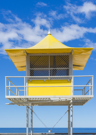 lifeguard tower: Bright yellow lifeguard patrol tower against the blue sky background