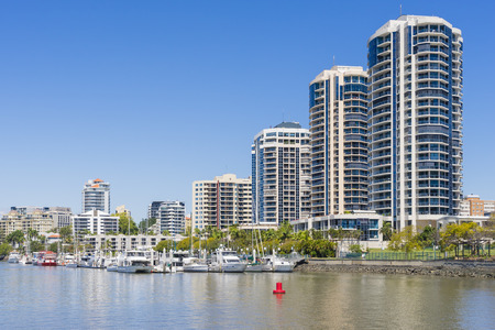 waterfront property: Modern waterfront apartments and yachts in marina in Brisbane during daytime