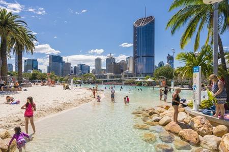 Brisbane, Australië - 25 september 2016: De mening van mensen zwemmen in the Streets Beach, binnenstedelijke en door de mens aangelegd strand, met wolkenkrabbers op de achtergrond in South Bank, Brisbane. Redactioneel