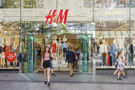 hm: Brisbane, Australia - September 26, 2016: View of a young woman walking out of H&M store in Brisbane. H M is a well-known international fashion retail corporation.