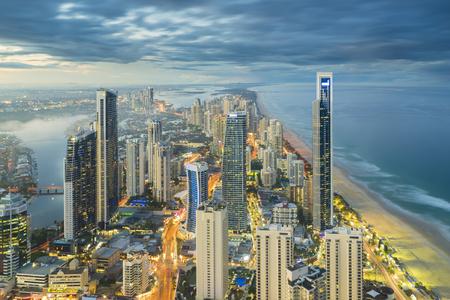 Luftaufnahme der modernen Gebäude mit Lichtspur am Flussufer an der Gold Coast, Australien bei Sonnenuntergang