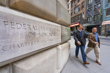 Uomo che cammina oltre la Federal Reserve Bank di New York Editoriali