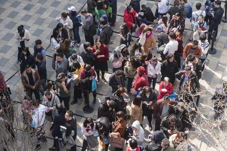 Mensen staan in de rij voor een evenement in een winkelcentrum in Peking