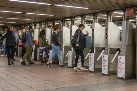 Pendler, die in einer U-Bahnstation in New York City durch die Drehkreuze fahren