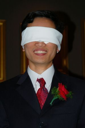 blindfolded: Man in suit, wearing a boutonniere, blindfolded and smiling.
