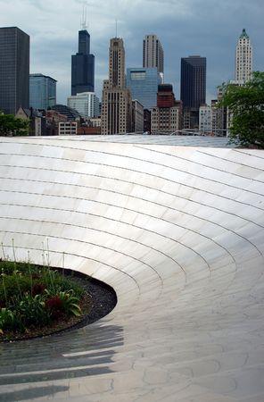 Metal Curve, onderdeel van het Millennium Park structuur: Chicago Skyline achter. Stockfoto