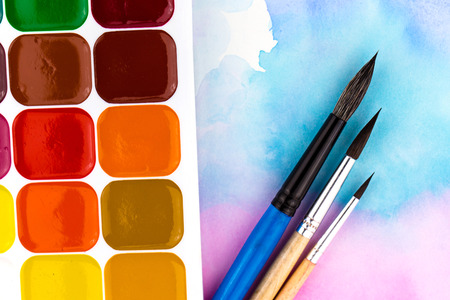 A palette of watercolor paints, brushes and paper for watercolors with colored spots. Flat lay style. Banque d'images
