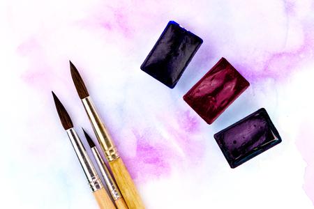 Une palette de peintures à l'aquarelle, pinceaux et papier pour aquarelles avec des taches colorées. Style plat. Banque d'images - 91512581