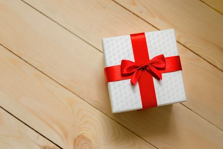 Gift box with red ribbon on wooden background. Stock Photo