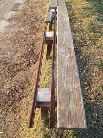 ballpark: An almost broken wooden bench at a ballpark