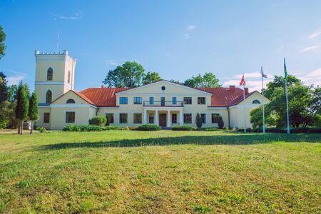 City Dzerbene, Latvia. Old manor house and meadow, green trees. Travel photo 2018.