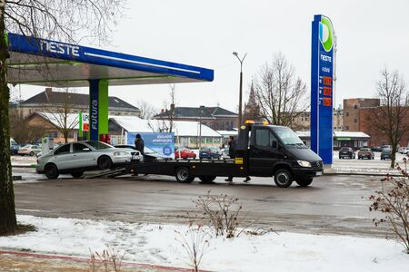 City Cesis, Latvia. Tow truck and broken volvo car at street. winter and snow, fuel station. Urban travel photo 2018, 28. december.
