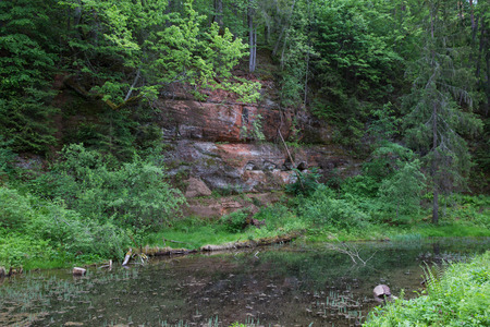 City Cesis, Latvian Republic. Red rocks and water.  Green and overgrown forest. Jun 1. 2019 Travel photo.