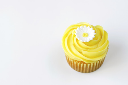 One yellow cupcake with daisy decoration