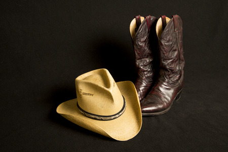 cowboy: Cowboy boots and cowboy hat on black background