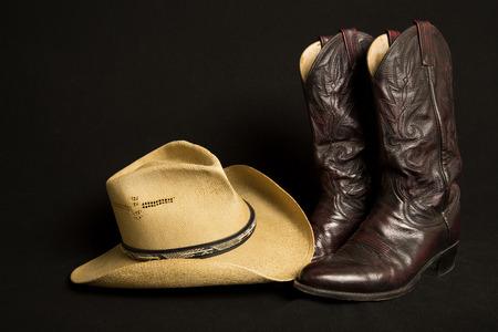 vaquero: Las botas de vaquero y sombrero de vaquero en el fondo negro Foto de archivo
