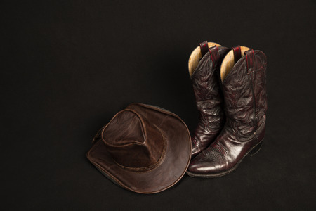 western usa: Cowboy boots and cowboy hat on black background