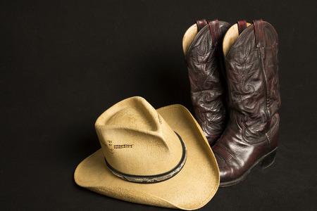 botas vaqueras: Las botas de vaquero y sombrero de vaquero en el fondo negro Foto de archivo