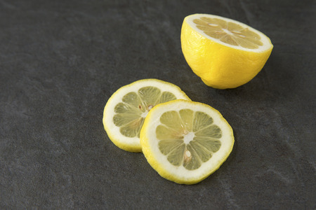 two and a half: Half of a lemon with two slices on slate background Stock Photo