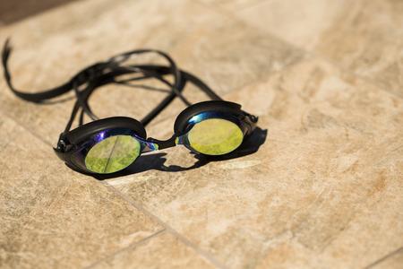 swim goggles: Gafas de nataci�n en el fondo del azulejo