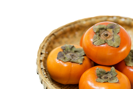 cor: Fresh ripe persimmons on Japanese bamboo basket