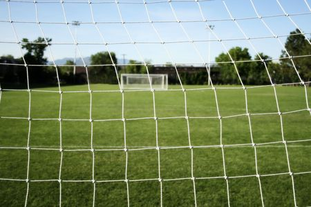 a footballsoccer goal netting with practice field in the background photo