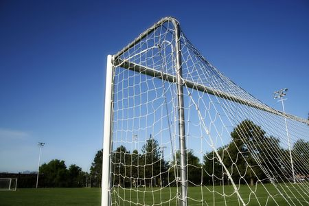 A low-angle photo of a soccer goal with practice field in the background photo