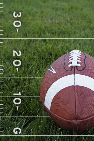 grassy field: A close-up view of an american football on a grassy field with yardage markings (vertical) Stock Photo