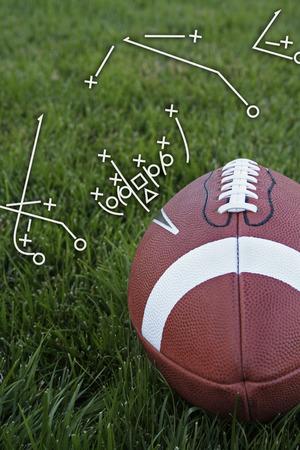 Een close-up weer van een American Football op een met gras begroeid terrein met een playbook tekening (verticaal) Stockfoto