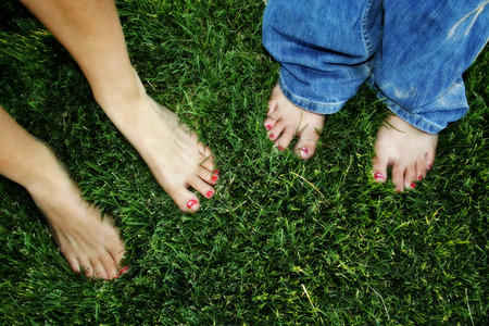 Flower-painted toenails standing on beautiful green grass photo