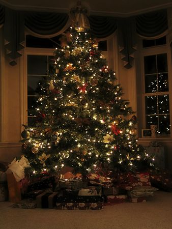 A decorated Christmas Tree on Christmas Eve night surrounded by presents Imagens