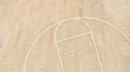 Basketball floorboards with an outline of three-point line and free-throw line and other court markings Stock Photo