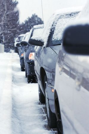 gridlock: Snow falls on a row of parked cars with snowy streets Stock Photo