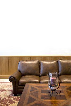 floorboards: Un atractivo sal�n-sala de espera con el establecimiento de cuero elegante sof� y mesa de caf�. El establecimiento cuenta con una pared blanca y elegante de madera de madera floorboards.  Foto de archivo
