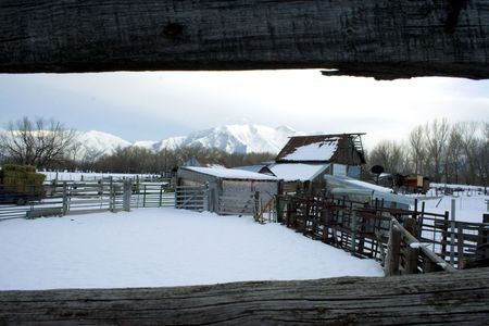 A wintertime scene of a snow-covered old barn and white rocky mountains in the background framed by old weathered wood from a fence photo