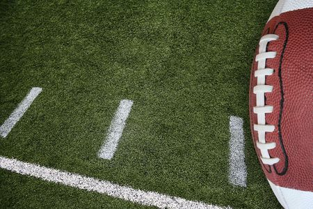 american football background: A photo of an American Football field yardage markings with a football on the right border Stock Photo