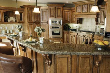 組み込みの木製家具と大理石のカウンター トップ、エレガントなストーブを備えた素朴なカントリー キッチンのインテリア 写真素材