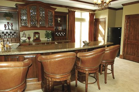 The interior of a home bar with built-in wooden cabinetry and marble countertops Stock Photo