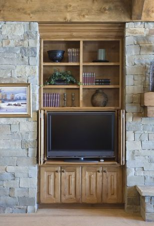 custom built: Built-in Entertainment Center in an elegant home with a stone wall