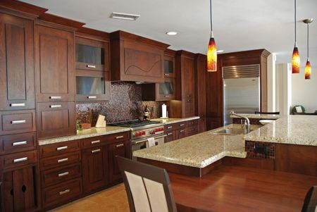 An interior view of an elegant custom-built kitchen with wood cabinetry and marble counters